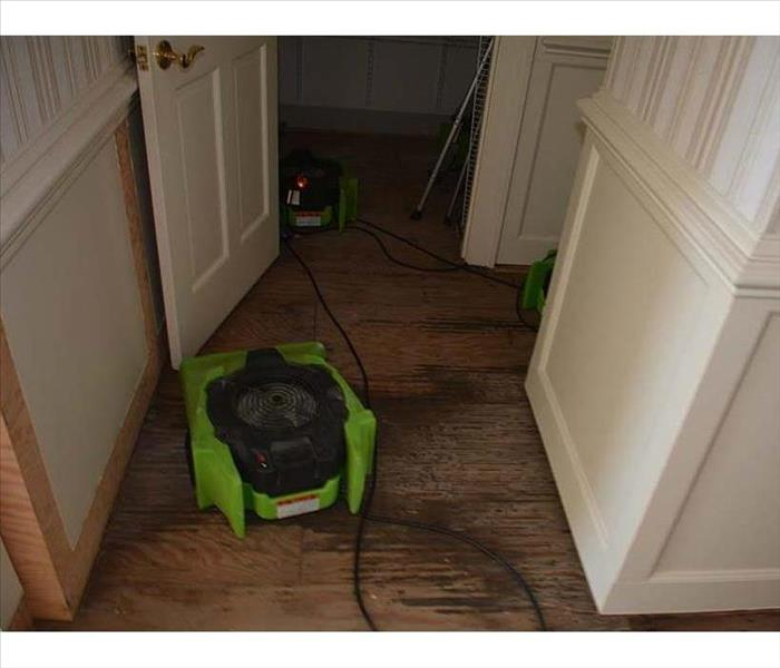 Green air movers drying out hallway area on plywood sheathing
