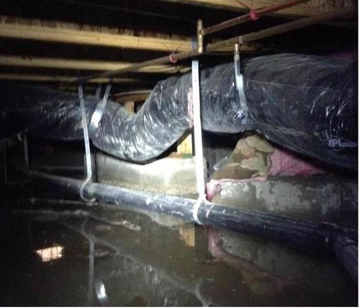 water covering crawlspace with pipes and ducts visible