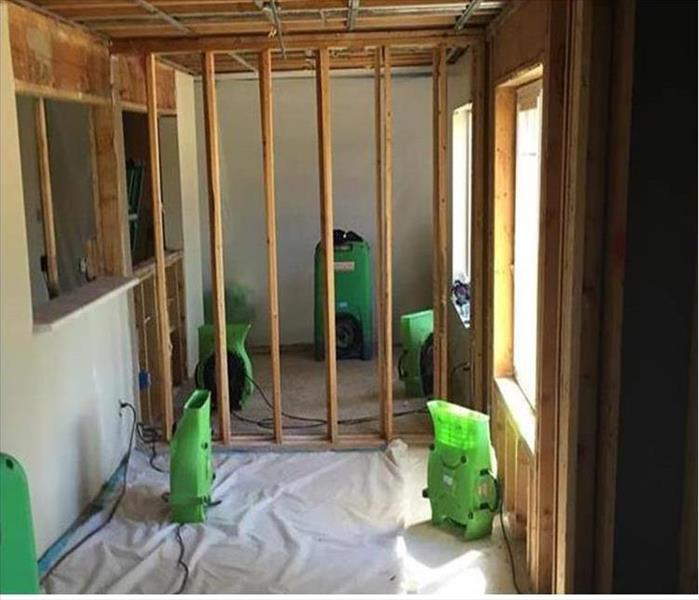Drywall material removed from walls and ceiling, showing the framing. Green equipment on poly sheeting on the floor